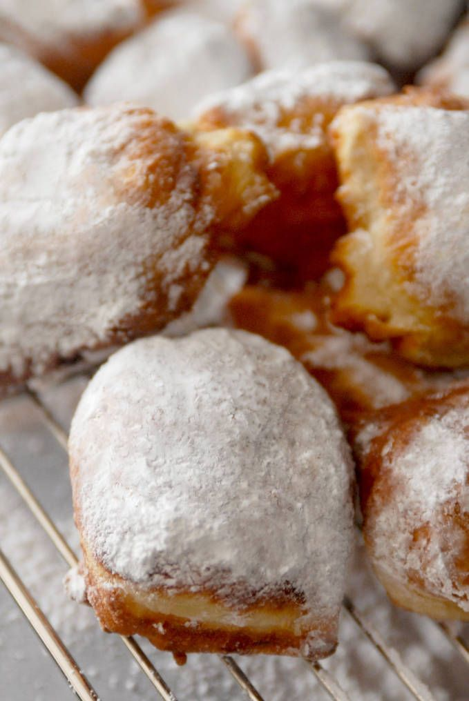 Buttermilk beignets dusted with icing sugar. Don't you just want a bite? They're super simple to make, and if you click to get the recipe you can eat 'em tonight!