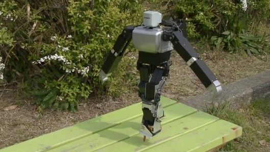 A roboticist has programmed a hobby humanoid robot kit to balance on a pair of thin stilts.
