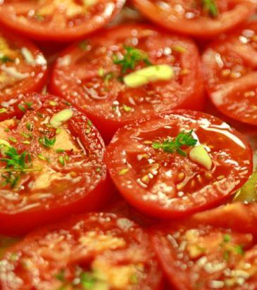 Στρώνουμε τις ντομάτες σε ένα ταψί με λαδόκολλα. Πασπαλίζουμε με τα υπόλοιπα ομοιόμορφα πάνω στις ντομάτες και ψήνουμε σε προθερμασμένο φούρνο στους 120°C μέχρι να συρρικνωθούν και να χάσουν τα περισσότερα υγρά τους. Αφήνουμε να κρυώσουν και ψιλοκόβουμε. Διατηρούμε στο ψυγείο.