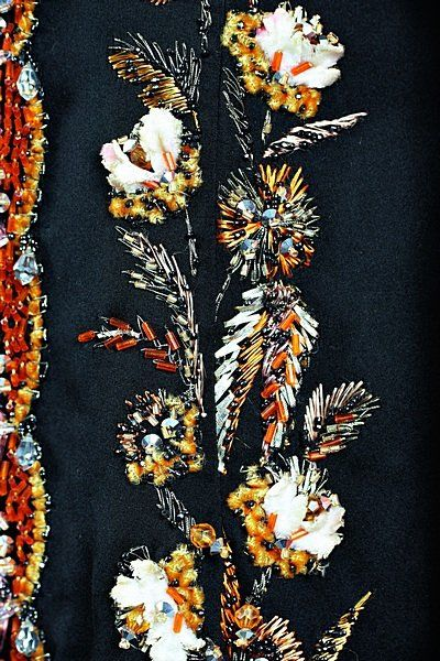 Pierre Balmain couture evening gown 1960 black satin sheath with corset empire-line bodice, embroidered by Lesage with three dimensional flower sprays and leaves in coral coloured chenille and floss silk, silver frisé strip and silver thread, facetted crystal beads in silver and coral, the bodice edge and skirt centre-front with double undulating bands of coral bugle beads and ivory velvet petals, pendant crystals, the skirt sprigged overall with flowerheads, matching organza backed satin…