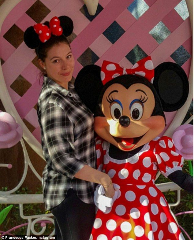 'Discussing bows, polka dots, and the other important things in life': Francesca Packer Barham posed with a Minnie Mouse character while visiting California's Disneyland on Wednesday with her beau Kelli Holland