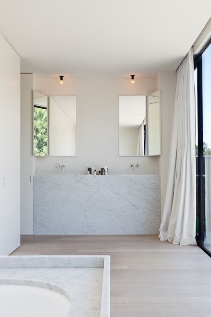 White bathroom with concealable vanity mirrors. Photo by Tim Van de Velde.
