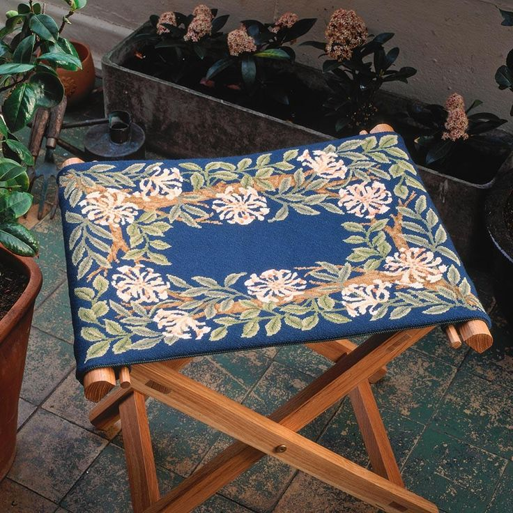 Honeysuckle Border (blue background). Beth Russell has adapted Honeysuckle so that it can be made into a comfortable cushion, a stool top or, if turned upright, into a firescreen.  A chart is provided for initials to be stitched in the central area