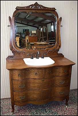 American Oak serpentine antique dresser fitted with sink and bronze faucet for a charming bathroom. American made and re-purposed..hope they put a water proof finish on it, or they will have water problems!