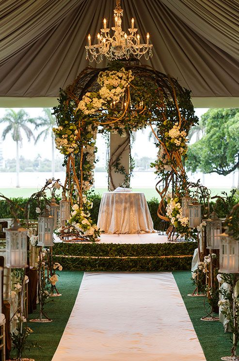 An enchanted wedding altar features a chuppah overgrown with vines and beautiful flowering white flowers.