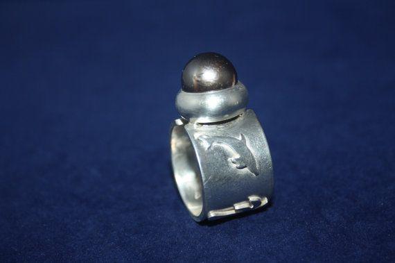 Dies ist mein persönlicher Ring (d.h. es ist ein Musterring).  Dieser Ring ist mit Palmen und Delphinen und einer wundervollen Tahiti Perle versehen.  Dieser Ring ist mit anderen Edelsteinen und in anderen Materialstärken und -strukturen umsetzbar. Grundsätzlich sind die Werke der Design-Kollektion aber einzigartig und sollen Euch inspirieren. Preise der Schmuckstücke sind immer abhängig vom verwendeten Edelstein und der Silbermaterialstärke.  Gerne bespreche ich mit Euch, welche Eurer…
