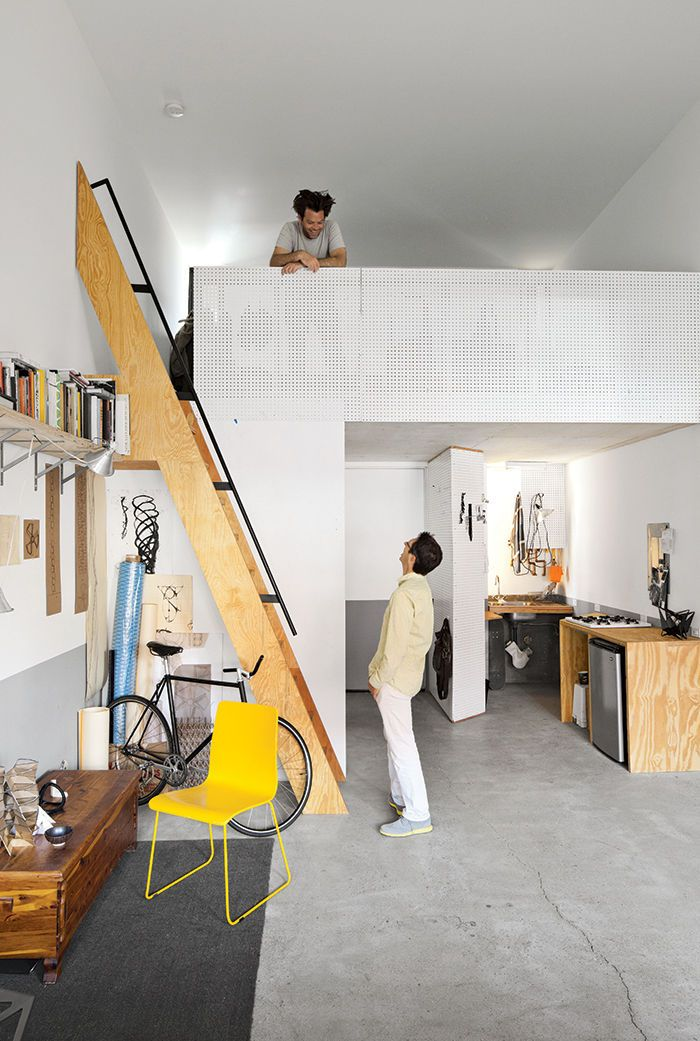 Modern micro-living unit with a pegboard mezzanine / From the mezzanine of his 450-square-foot apartment at La Esquina, an eight-unit live-work building in San Diego's Barrio Logan neighborhood, designer, artist, and Woodbury University professor Patrick Shields chats with fellow professor Hector Perez, who spearheaded the project.