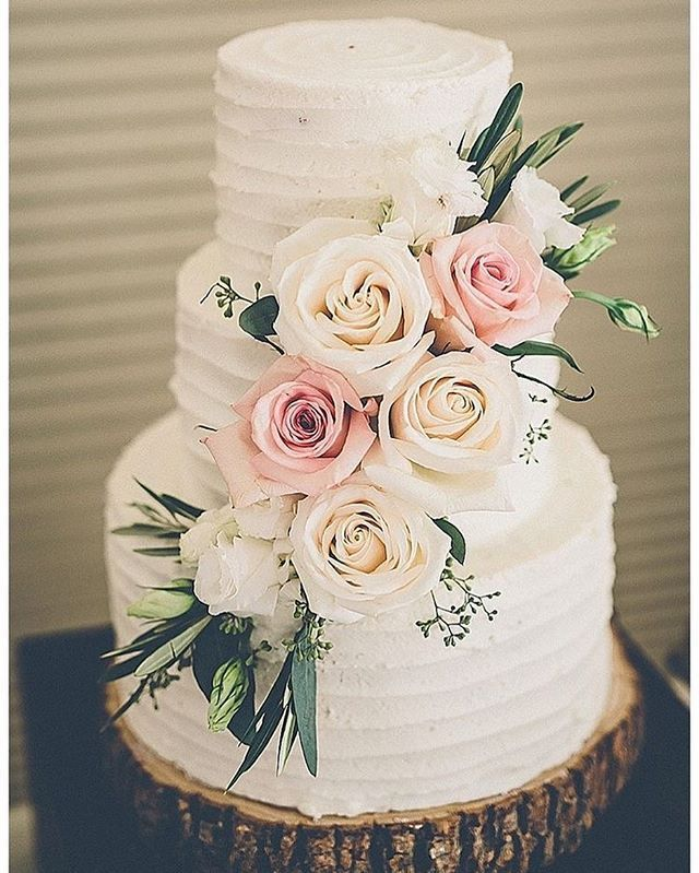 Rustic wedding cake adorned with blush florals on wood slice cake stand #weddingcake #rusticwedding #rusticweddingcake