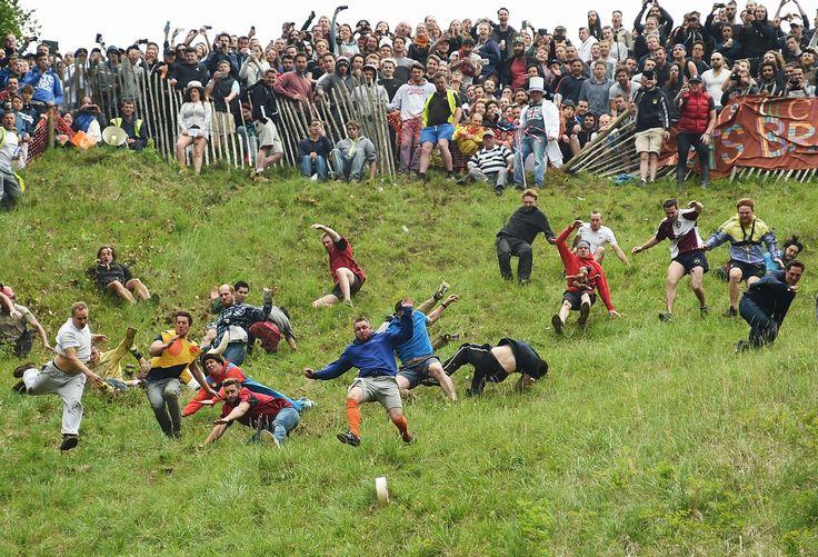Deelnemers aan de jaarlijkse kazenjacht bij het Engelse Brockworth in het zuidwestelijke graafschap Gloucestershire. Al sinds het begin van de negentiende eeuw wordt deze 200 meter lange race gehouden, waarbij mannen op een steile helling zo snel mogelijk achter een naar beneden rollende ronde kaas van 3,6 kilo aanrennen.