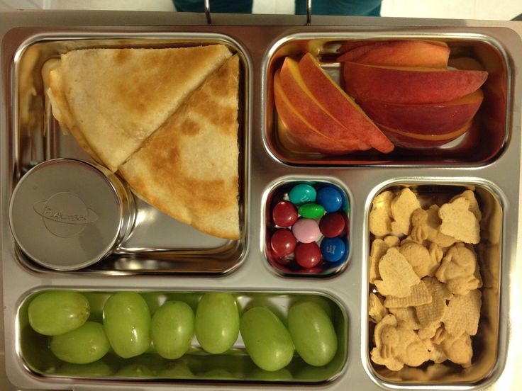 Planet box lunch: cheese quesadillas, grapes, peaches, Annie's bunnies, m&m's.