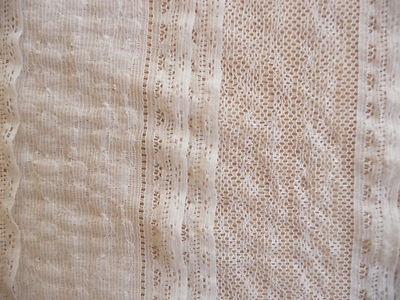 Cremefarbene edle Spitze.  Der Stoff besteht zu 62% aus Baumwolle, 30% aus Polyamid und 8% Elastan.  Die Spitze ist weich, leicht und hat einen wunderbaren Fall.  Die Baumwollspitze ist in alle Richtungen dehnbar. Die einzelnen Streifen sind ca 8,5 cm breit und die Rüschen sind ca. 2,5 cm breit  Der Spitzenstoff liegt 1,30 cm breit.   Aus dem Baumwollstoff lassen sich Blusen, Kleider, Tuniken, Mantel, Jacken, Röcke, Kissen, Decken, Gardinen und vieles mehr herstellen.