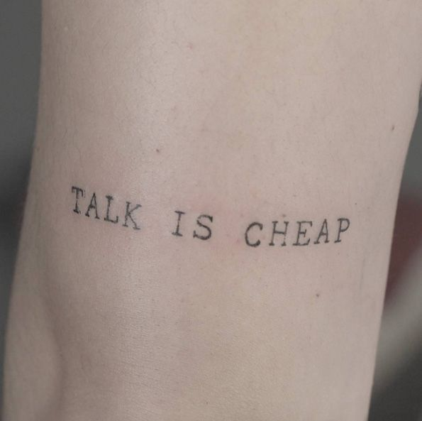 'Talk is cheap' typewriter font tattoo by Lindsay April