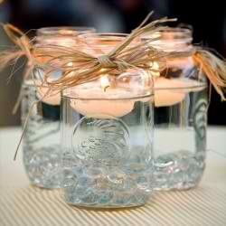 perfect inexpensive centerpieces - Mason Jars, Clear Pebbles, Water, Floating Candles, and Raffia! Make sure the raffia is nowhere near the flames :)