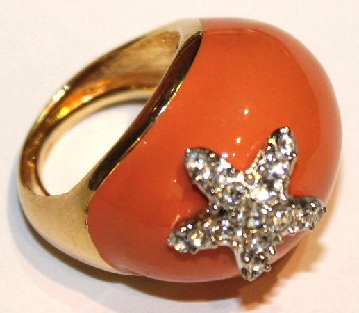 Grande anello regolabile firmato Kenneth Lane, con resina corallo e stellina illuminata da cristalli swarovski.