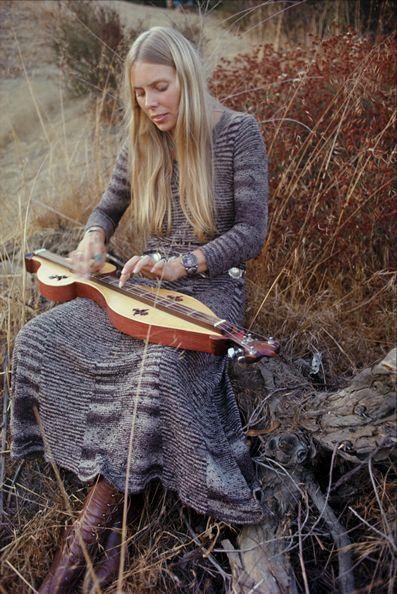 Joni Mitchell playing the dulcimer outdoors.