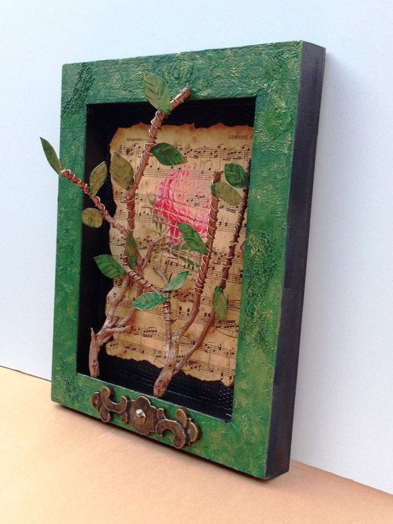 WALL ART [or could be placed on a shelf]  Handmade one-of-a-kind art display. Mixed media design with a birch wood panel as the base. The surface is textured and painted black and shades of green. The design is inset, similar to a shadow box.  Natural curved tree branches with bronze wire and cut metal green leaves are the main focus of the design. A background paper design (music notes and fractured flower) partly overlays the black surface. A vintage metal accent plate is secured at the…