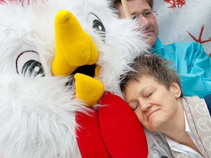 Die Fraktionsvorsitzende der Grünen, Renate Künast, kuschelt auf einer Pressekonferenz in Berlin mit einem Hühner-Maskottchen. Foto: dpa / Sebastian Kahnert.