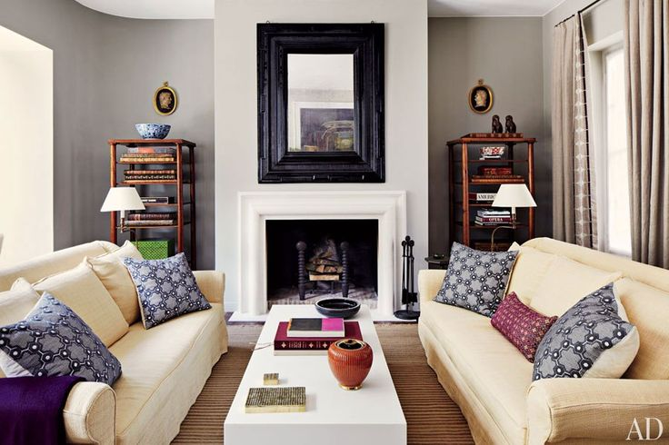 Interior designer Timothy Whealon transformed an early-20th-century Monaco residence into a casual home for an insurance executive and a documentary filmmaker. At one end of the living room, an understated gray wall color works in harmony with lively patterned throw pillows and a subtle striped rug. (May 2012)
