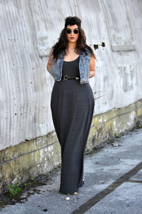 Chica plus size usando un maxi vestido en color negro con una chaqueta