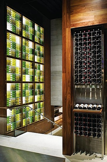 Empty wine bottles backlit by LED fixtures form a ...