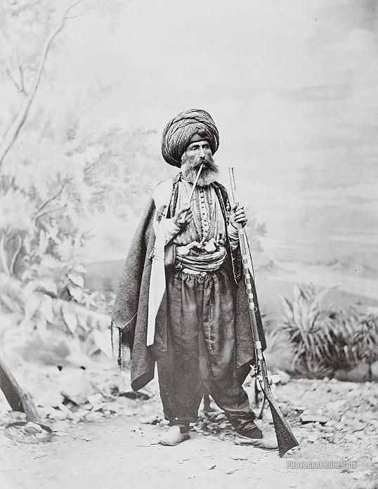 Chaldean man in traditional Turkish costume, posed before a backdrop, holding rifle and smoking a pipe. Istanbul, Turkey. 1869.
