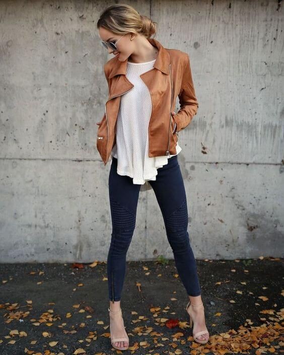 Woman wearing blue skinny jeans, white draped top, brown leather jacket and nude strappy heels