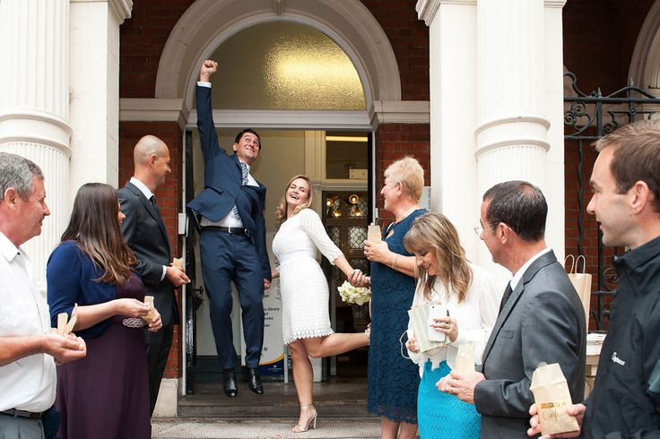 Mayfair Library wedding photographer Emma Duggan photographs civil marriage ceremonies throughout London. This bride and groom are leaping for joy after their wedding in the Marylebone Room. Afterwards they had family group photos in the adjacent Mount Street Gardens.