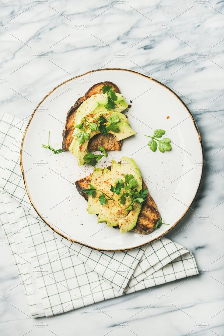 #Flat-lay of avocado toast over marble background top view Healthy vegan breakfast or lunch. Flat-lay of avocado toast on plate over grey marble background top view. Clean eating detox weight loss vegetarian dieting food concept