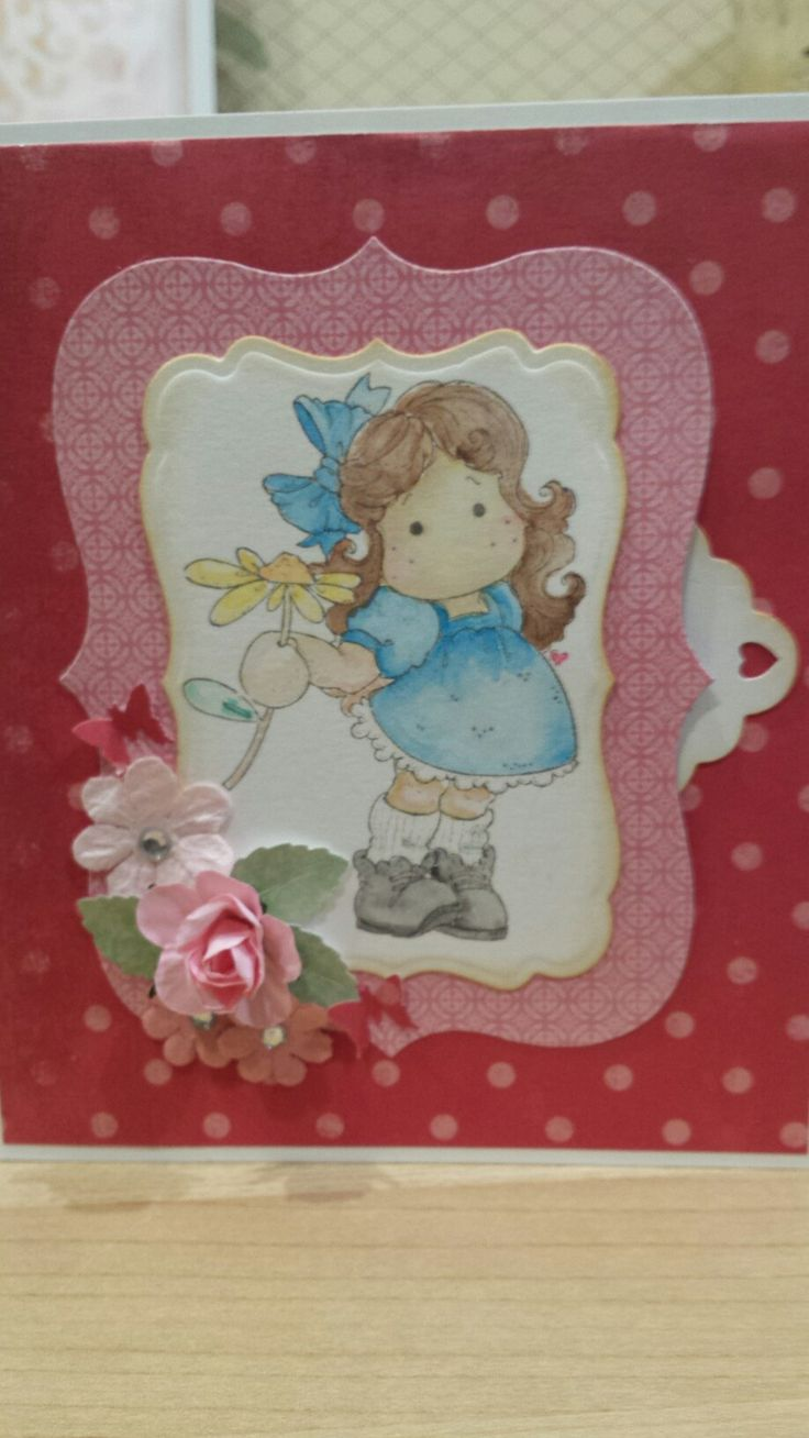 Tilda with Flower. Image on die cut shape, layered onto card. Side of image left open to house message tag. Hand coloured using Distress Inks.