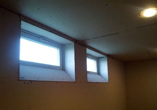 Make windows look larger. angled drywalled basement window idea More