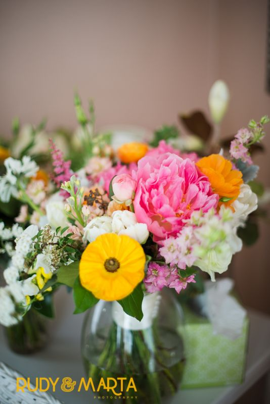 detail of bright and cheerful bridal bouquet highlighted by coral charm peonies, orange ranunculus, peach campanella roses, spirea, peach stock, white lisianthus and parrot tulips.