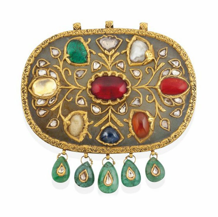 A LARGE NAVRATNA GEM-SET JADE PENDANT NORTH INDIA OR DECCAN, 19TH OR EARLY 20TH CENTURY Of oval form, typically inset with nine different gems, overlaid in gold with floral sprays and diamond-set buds, five drop-shape emerald pendants along the lower edge possibly added later, the reverse applied with gold borders finely engraved with meandering flowery vine, three hanging loops at top 3 1/8in. (8cm.) across