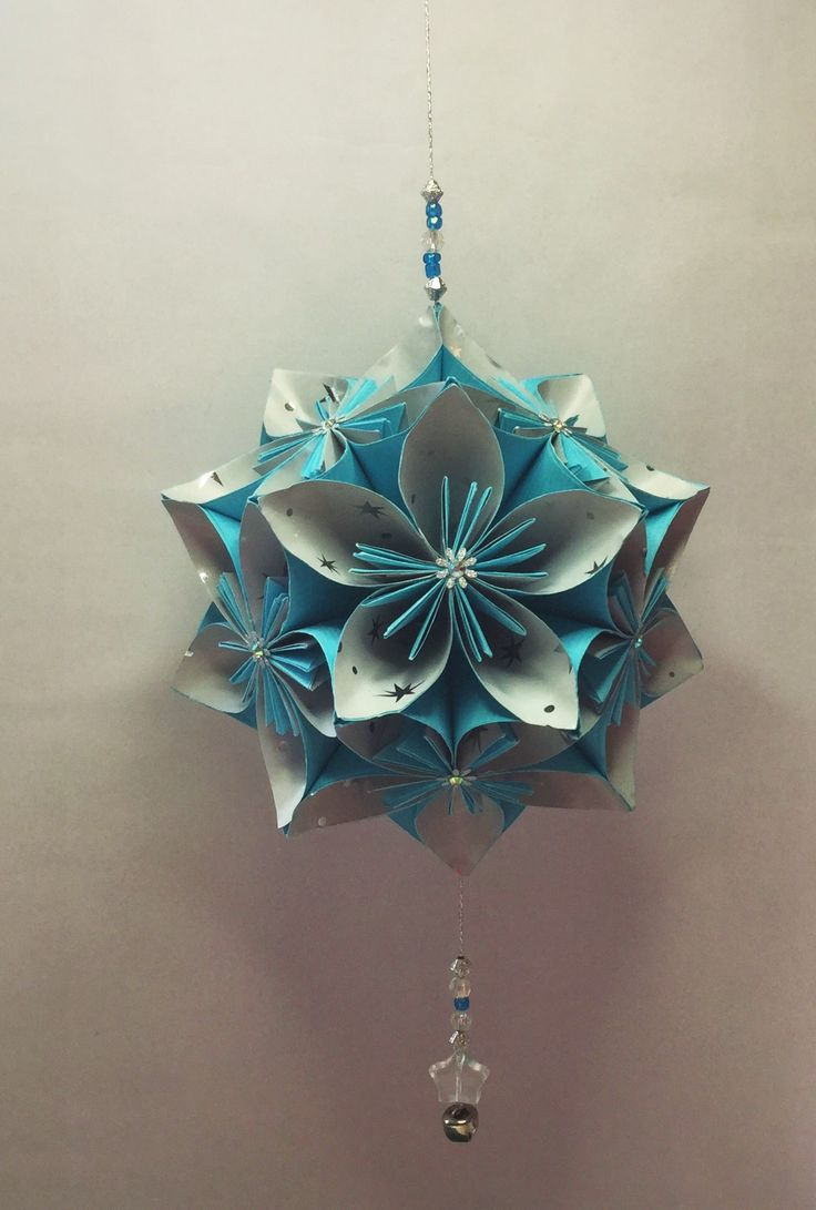 KO29  Light blue with silver stars inner petal..hanging beads and small silver jingle bell....14cm sq.