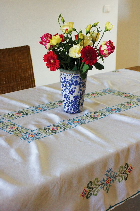 Large linen tablecloth, prettily hand embroidered with a cross stitch design. There are 10 napkins which are also embroidered with a motif and