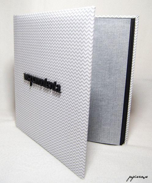 Album do wklejania zdjęć.  Album posiada 20 czarnych stron (10 kart) o wymiarach 24x24 cm. Okładkę zdobi bawełniana tkanina w szaro-biały zygzak, a także czarny, drewniany napis...