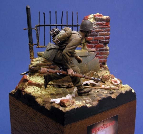 figurka biegnącego żolnierza na podstawce z gruzowiskiem