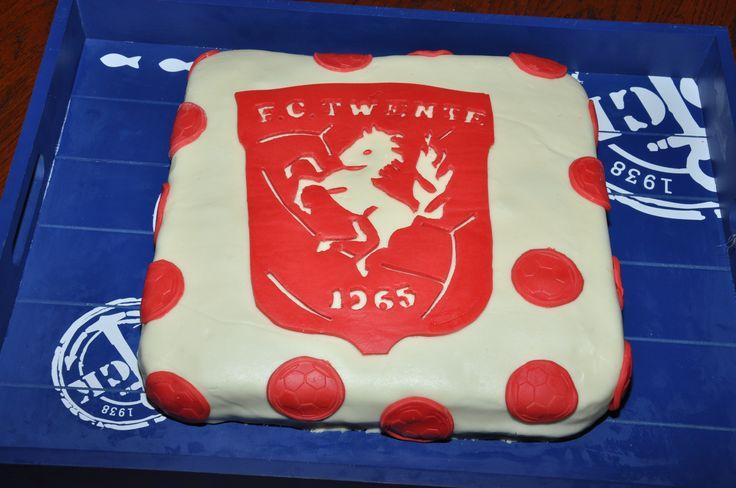 F.C. Twentetaart, deze taart heb ik zelf gemaakt door de hele taart te bekleden met (zelfgemaakte) witte fondant. Daarna met rood fondant het logo uitgesneden en alle stukjes die wit moeten blijven eruit gesneden. Voor de verjaardag van een grote fc. Twente fan.