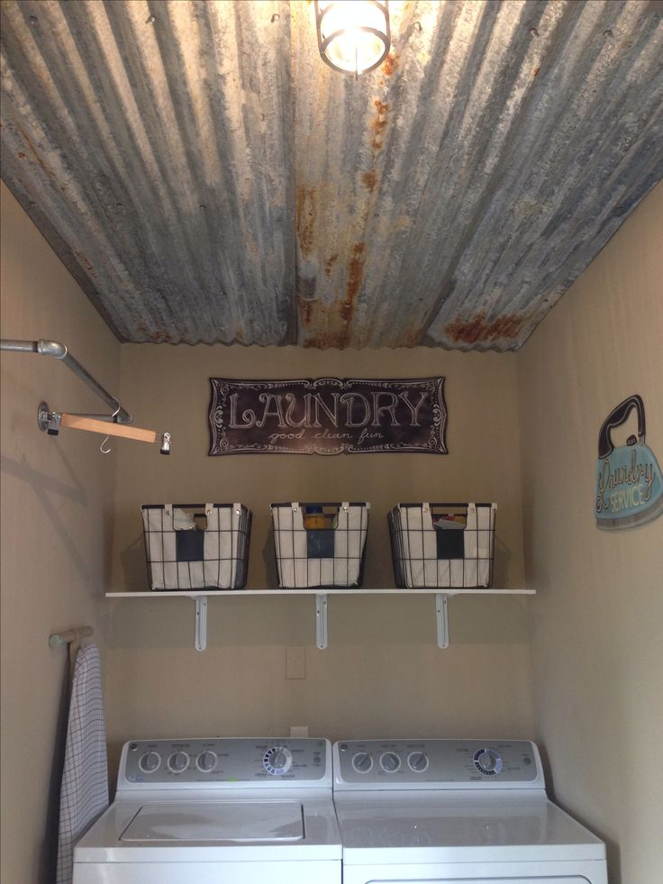 Our laundry room with rustic tin ceiling, industrial light and clothes rod.