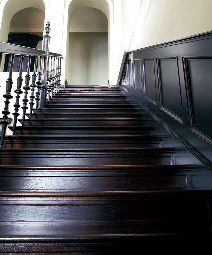 www.trabczynski.com  ST087 Schody policzkowe ze stopnicami nakładanymi na policzki, wykonane z dębu wędzonego oraz dębu malowanego farbami kryjącymi. Balustrada z tralkami toczonymi, ze złoconymi zdobieniami. Schodom towarzyszą płycinowe boazerie / ST087 Cut string stair made of smoked oak and solid painted oak. Balustrade with lathed banisters, with gilt decorations. The stairs accompanied by panelling