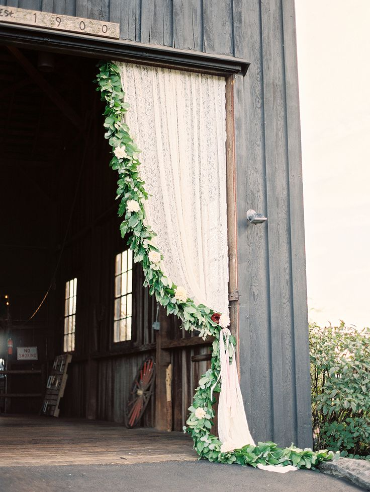 Barn wedding with curtain and floral garland. Photography : Sweetlife Photography Read More on SMP: http://www.stylemepretty.com/oregon-weddings/west-linn/2016/04/05/an-1887-farmhouse-played-host-to-this-rustic-garden-wedding/