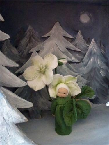 Christrosenblumenkind - auch eine tolle Idee: der Hintergrund mit den verschneiten Tannen aus Holz/Pappe (?)