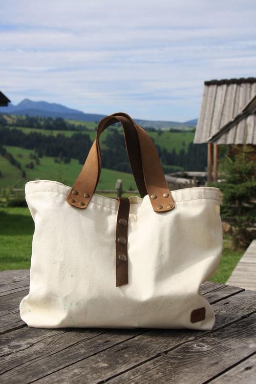 Tote-bag z tkaniny z grubymi, skórzanymi rączkami.