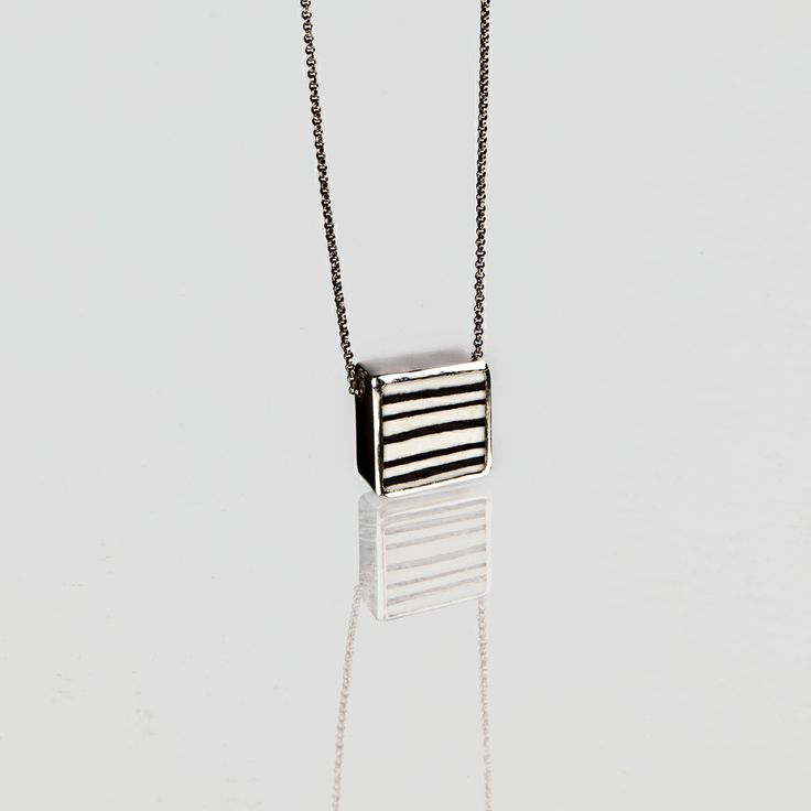 pendant in porcelain and silver, porcelain tecnique : neriage; the striped porcelain piece is set on silver one of a kind