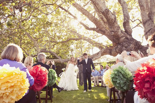 bride and groom raise arms as they walk down aisle lined with colored pom-poms