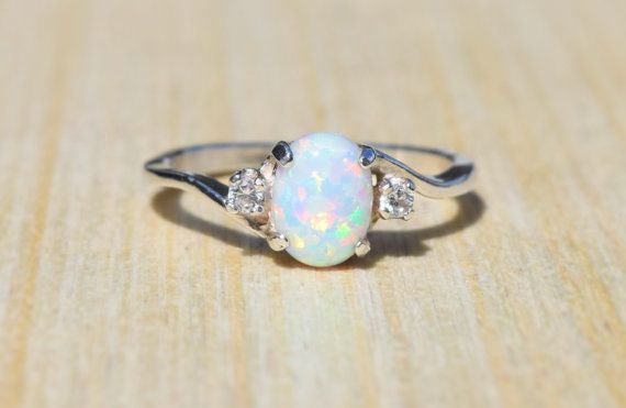 Stunning white lab opal with cubic zirconia accent stones, hand set in a sterling silver setting. Pictured with White - April side stone color.  ***PLEASE NOTE: This is custom ring. Due to the fact that each of these rings is made to order, I do not accent returns or exchanges on anything other than the ring as it is pictured. (White opal with white accent stones)  Band Material: 925 Sterling Silver Center Gem: White Lab Opal Center Gem size : 8mm x 6mm Side Gem: Cubic Zirconia Side Gem…
