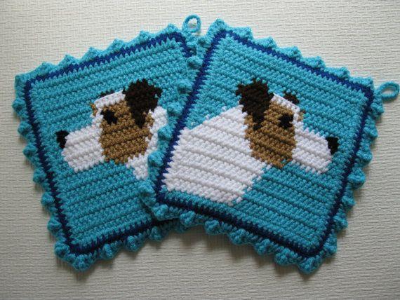 Handgemaakt, Jack Russell Terrier sierpotten. Set van twee, hond sierpotten. De terriërs zijn haakwerk in wit en warm bruin op een heldere turkooizen achtergrond. De aansluitingen zijn chocolade bruin oren en een zwarte neus en ogen. Sierpotten zijn dubbel dik en het achterpaneel is hand breien op een weefgetouw in turkoois. Pannenlappen zijn omzoomd met blauw en afgewerkt met een turkoois gehaakt ruffle.  Sierpotten meet ongeveer 8 1/2 inch (21 cm) vierkant met een lus opknoping in de…