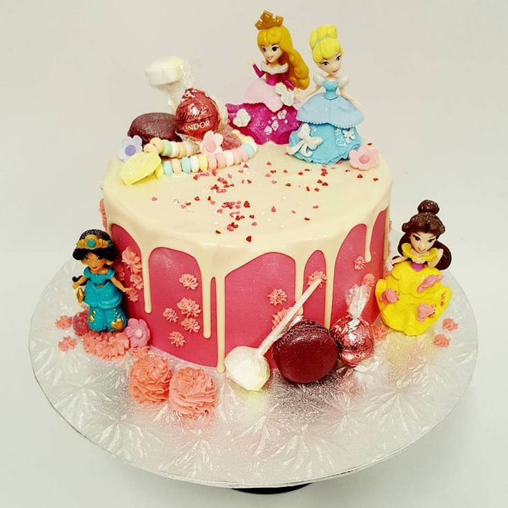Smooth bright pink cake with drip and Disney Princess Figurines