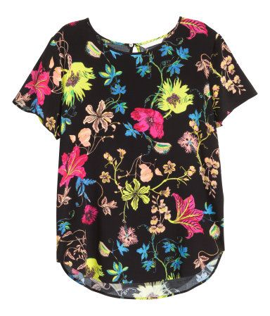 Black/Floral. Short-sleeved blouse in viscose crêpe weave with an opening with a button at the back of the neck and a rounded hem. Slightly longer at the