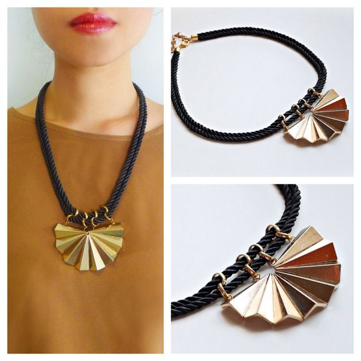 Black and gold necklace featuring gold tone center piece with black silk rope