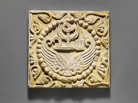 Wall panel with wings and a Pahlavi device encircled by pearls  Period: Sasanian Date: ca. 6th century A.D. Geography: Mesopotamia, Ctesiphon Culture: Sasanian Medium: Stucco Dimensions: H. 15 3/8 x W. 16 1/4 in. (39 x 41.3 cm) Classification: Stucco-Reliefs-Inscribed The Metropolitan Museum of Art : Not on view